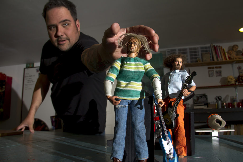 John Johnston reaches to adjust a miniature Kurt Cobain. (Kevin J. Beaty/Denverite)  denver; denverite; colorado; art; nirvana; kurt cobain