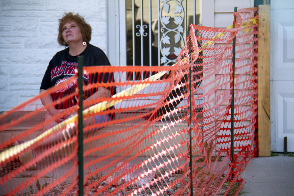 Fran Pope sits on the steps leading into the house she's owned for nearly 20 years. (Kevin J. Beaty/Denverite)