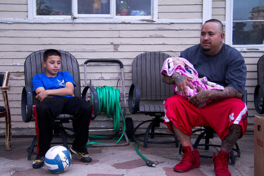 Mark Rodriguez sits with his month-old daughter and son outside of his rented home.  denver; colorado; chaffee park; highlands; kevinjbeaty; megan arellano; flip; development; homes; houses; property values; rent;