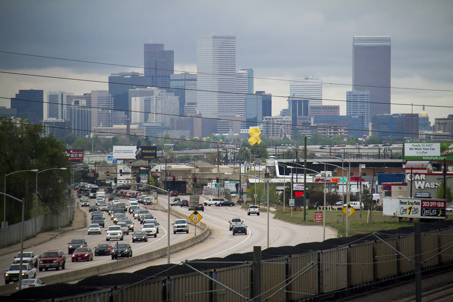 The Denver skyline as seen from the Evans Avenue bridge. (Kevin J. Beaty/Denverite)  skyline; cityscape; light rail; train; transportation; bars; food; dining; drinks; denver; denverite; colorado; kevinjbeaty