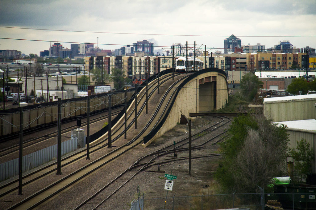 An RTD train crests over a bridge near Evans Avenue. (Kevin J. Beaty/Denverite)  light rail; train; transportation; bars; food; dining; drinks; denver; denverite; colorado; kevinjbeaty