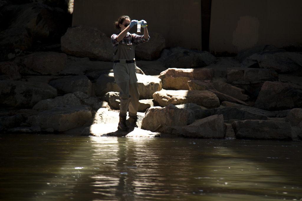 Denver Department of Environmental Health intern Meghan Schrik takes water samples from the Platte beneath Speer Boulevard. (Kevin J. Beaty/Denverite)  platte; cherry creek; river; water; health; environment; city; confluence park; denver; colorado; kevinjbeaty; denverite