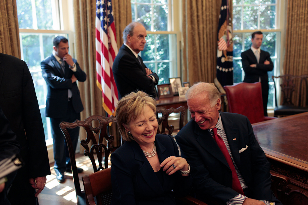 Secretary of State Hillary Clinton laughs at a remark by Vice President Joe Biden as they wait for the start of a press statement by President Barack Obama and Egyptian President Hosni Mubarak in the Oval Office Aug. 18, 2009. (Official White House Photo by Lawrence Jackson/Flickr)  hillary clinton; politics; creative commons; presidential race; election; white house; flickr; denverite
