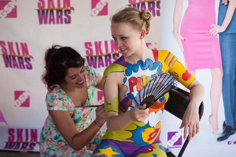 Season one Skin Wars winner, Natalie Fletcher, paints a Pride-inspired pop art mural on a fest attendee. (Chloe Aiello/Denverite)