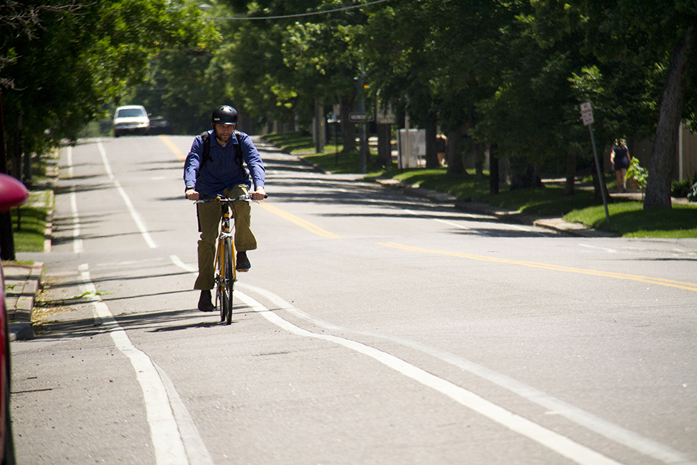 A biker cruises westbound on 16th Street. (Kevin J. Beaty/Denverite)  bike; sixteenth street; 16th street; city park west; kevinjbeaty; colorado; denver; denverite;