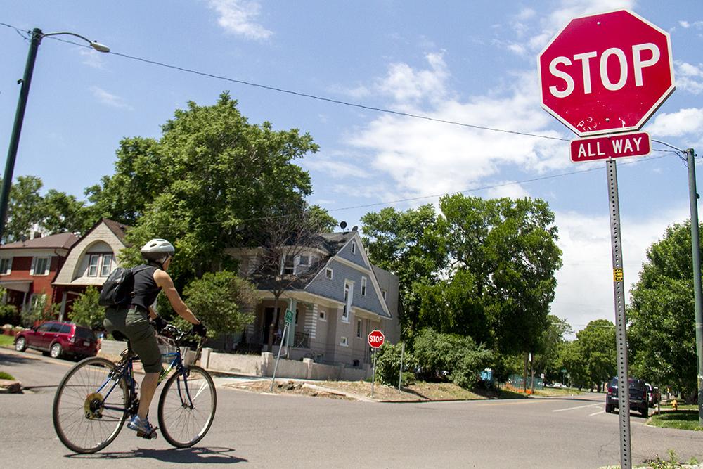 A biker blows through a four-way stop on 16th Street in City Park West. (Kevin J. Beaty/Denverite)  bike; sixteenth street; 16th street; city park west; kevinjbeaty; colorado; denver; denverite;