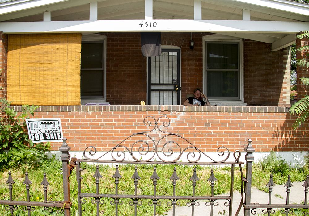 "Nathan Stickel sits on his porch in Globeville with a sign planted in his yard reading ""My community is not for sale."" (Kevin J. Beaty/Denverite)  globeville; denver; denverite; kevinjbeaty; colorado; gentrification;"