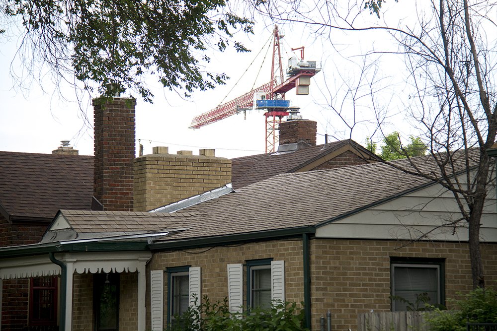 A crane stands tall beyond homes on Meade Street in West Highland, a reminder of the neighborhood's active renewal. (Kevin J. Beaty/Denverite)