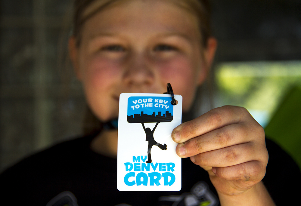 Piper Tribelhorn shows off her My Denver Card. (Kevin J. Beaty/Denverite)  my denver card; argo park; globeville; summer; pool; kids; kevinjbeaty; denver; denverite; colorado;