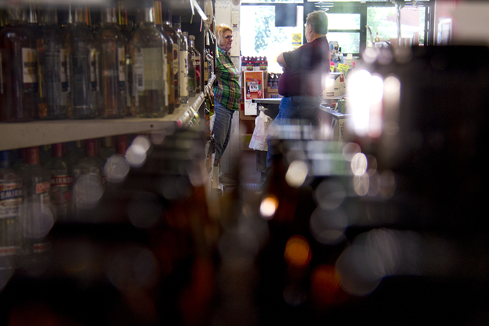 Logan Liquors owner Lore Spanbauer behind the counter of her small family-owned store in Denver's Speer neighborhood. (Kevin J. Beaty/Denverite)  logan liquors; retail; beer; kevinjbeaty; denverite; denver; colorado;