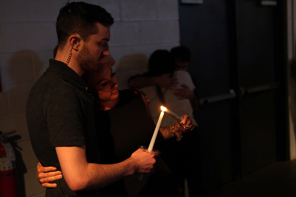 Tanner Edwards and Tara Ginnett share a flame at the vigil.