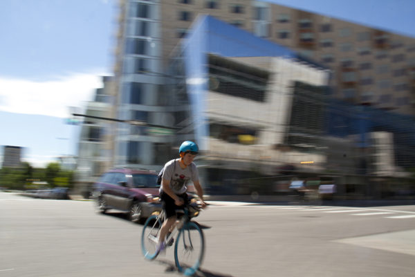 A cyclist rolls though the intersection at 12th and Broadway. (Kevin J. Beaty/Denverite)  bike; bicycle; denver; colorado; denverite; kevinjbeaty; broadway