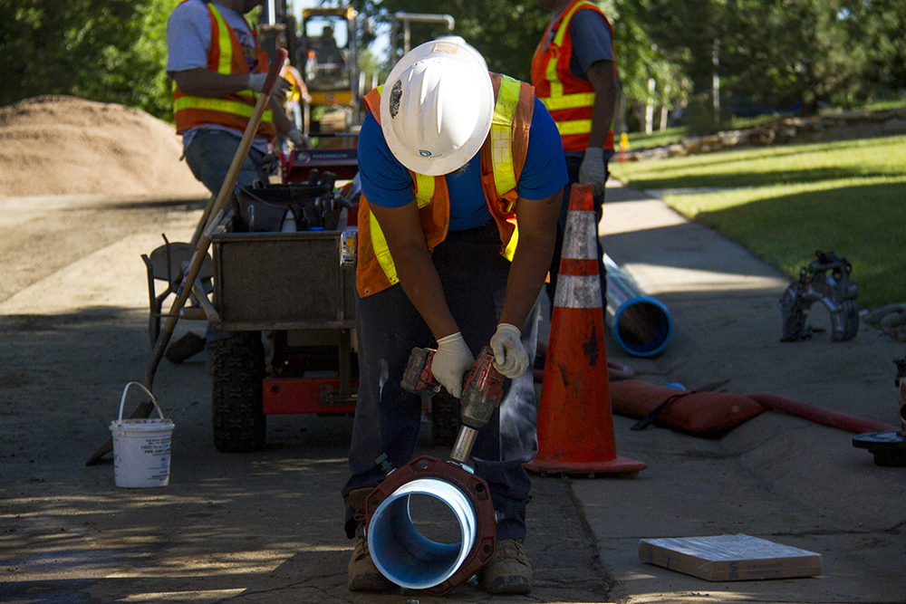 Denver Water workers prep a pipe for use beneath a Greenwood Village neighborhood street. (Kevin J. Beaty/Denverite)  denver water; infrastructure; pipes; kevinjbeaty; denver; colorado; denverite;