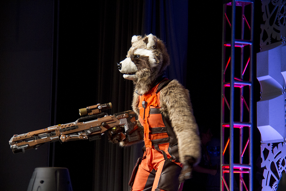 Guardians of the Galaxy's Rocket Raccoon brandishes a weapon on stage at the Denver Comic Con Cosplay Shindig on June 18, 2016. (Kevin J. Beaty/Denverite)  denver comic con; convention center; denver; colorado; denverite; kevinjbeaty