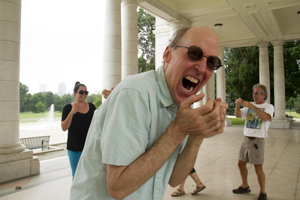 Jeff Johnston calckes during Laughter Yoga under the Walter Scott Cheesman Pavilion at Cheesman Park. (Kevin J. Beaty/Denverite)  park; summer; denver; denverite; colorado; kevinjbeaty