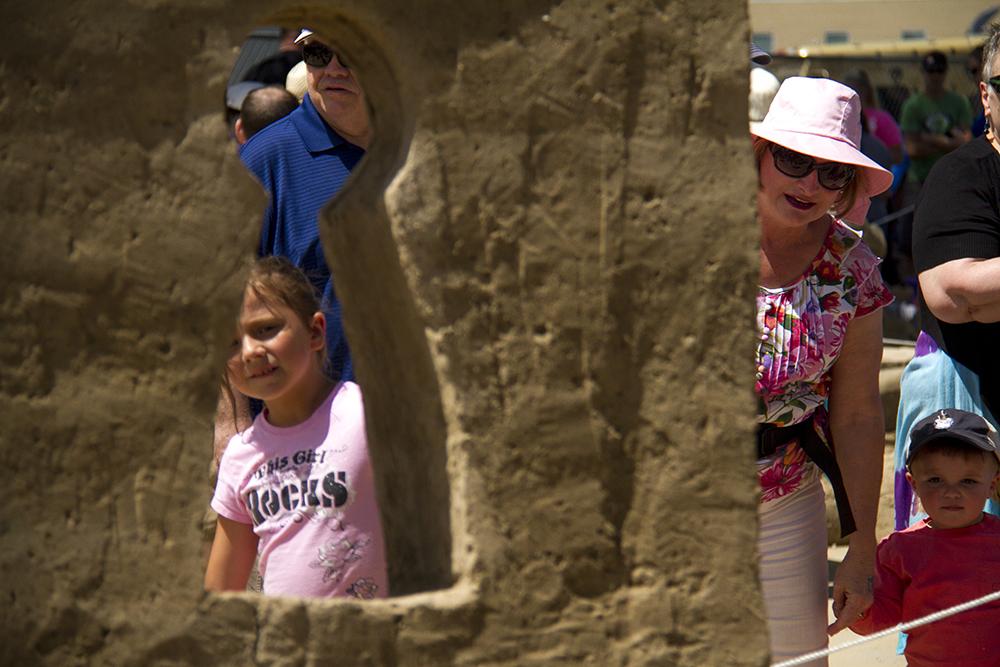 Festivalgoers peer through a sandy keyhole into a sandy living room at Arvada's Sand in the City festival on June 25, 2016. (Kevin J. Beaty/Denverite)  sand in the city; sand castle; summer; festival; arvada; denver; kevinjbeaty; denverite; colorado;