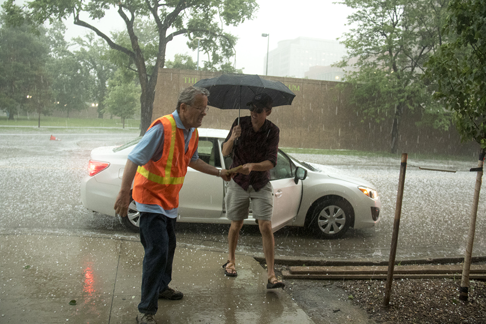 Tim Drago, a support judge, braves a roaring hailstorm to collect ballots from passing voters. (Kevin J. Beaty/Denverite)  hail; storm; rain; cowx; election; ballot; vote; denver; colorado; denverite; kevinjbeaty;