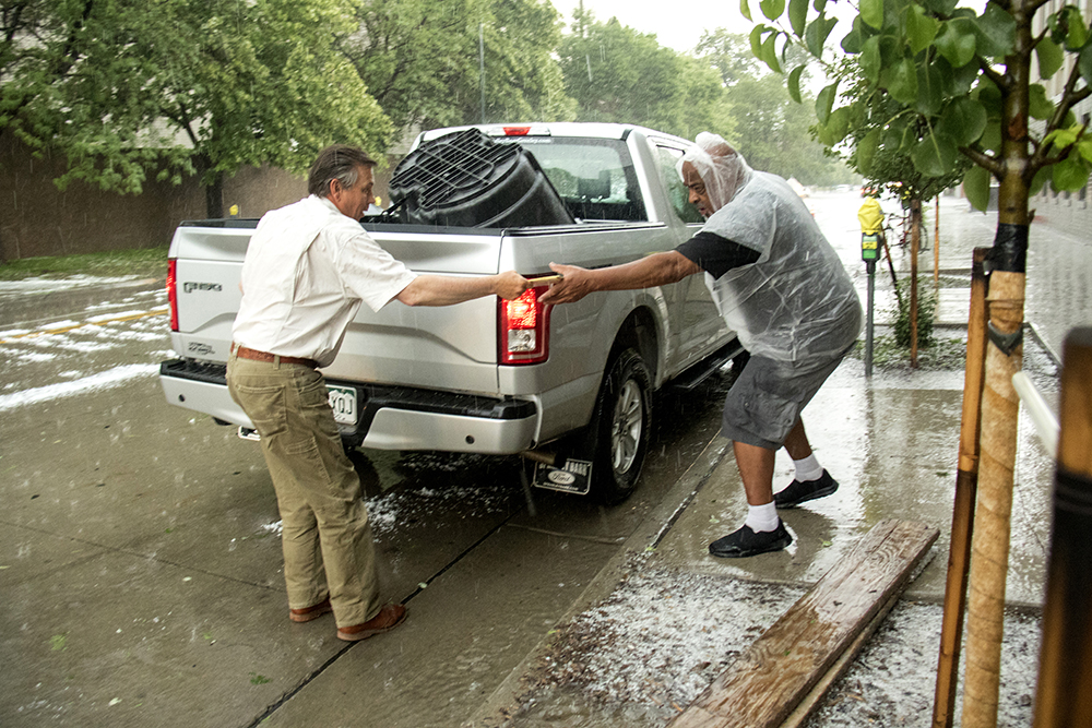 Ted Jefferson takes a quickly-passed ballot amidst a summer hailstorm right before polls closed. (Kevin J. Beaty/Denverite)  hail; storm; rain; cowx; election; ballot; vote; denver; colorado; denverite; kevinjbeaty;