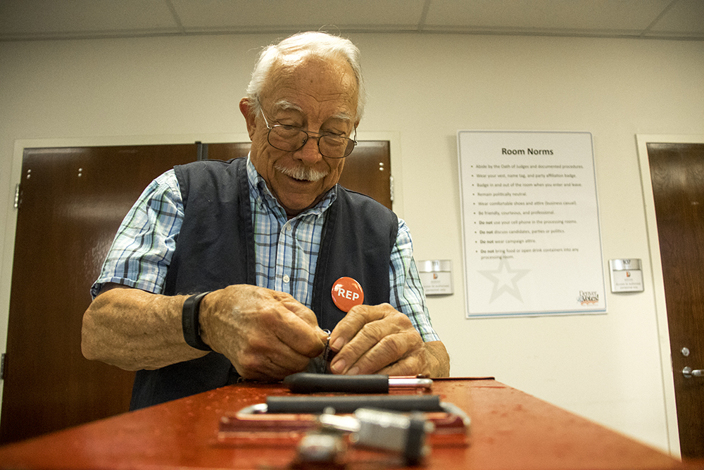 "Richard Bettinger, a ballot reception staffer and self-described ""flunkie"" unlocks a ballot box straight from a polling station. (Kevin J. Beaty/Denverite)  election; ballot; vote; denver; colorado; denverite; kevinjbeaty;"