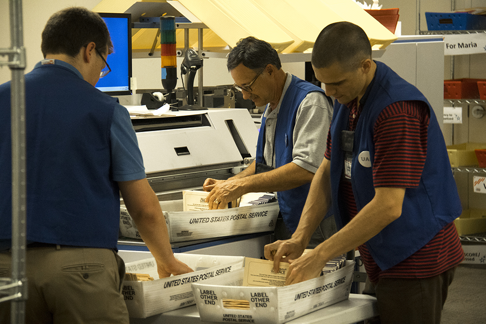 Ballot operations assistants stack ballots into a machine that will strip a sticker from the envelope and scan the signature beneath for individual verification. (Kevin J. Beaty/Denverite)  election; ballot; vote; denver; colorado; denverite; kevinjbeaty;