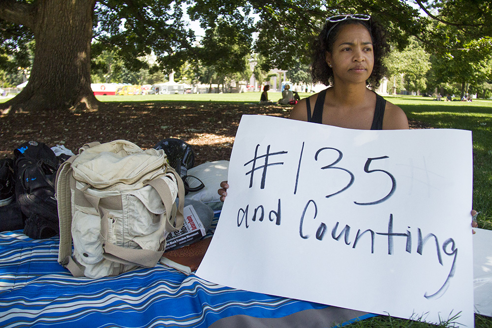 Amy E. Emery-Brown sits on the lawn across from Denver's City and County Building where she plans to stay for 135 hours in protest against police killings against 135 black peope this year and in solidarity with her community. (Kevin J. Beaty/Denverite)  black lives matter 5280; protest; civic center park; city and county building; amy e emery-brown; kevinjbeaty; denver; denverite; colorado;