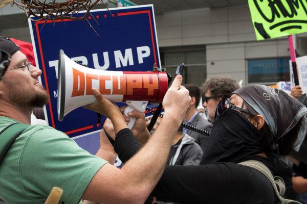 An anti-Trump protester blares music in the face of a Trump supporter. (Chloe Aiello/Denverite)