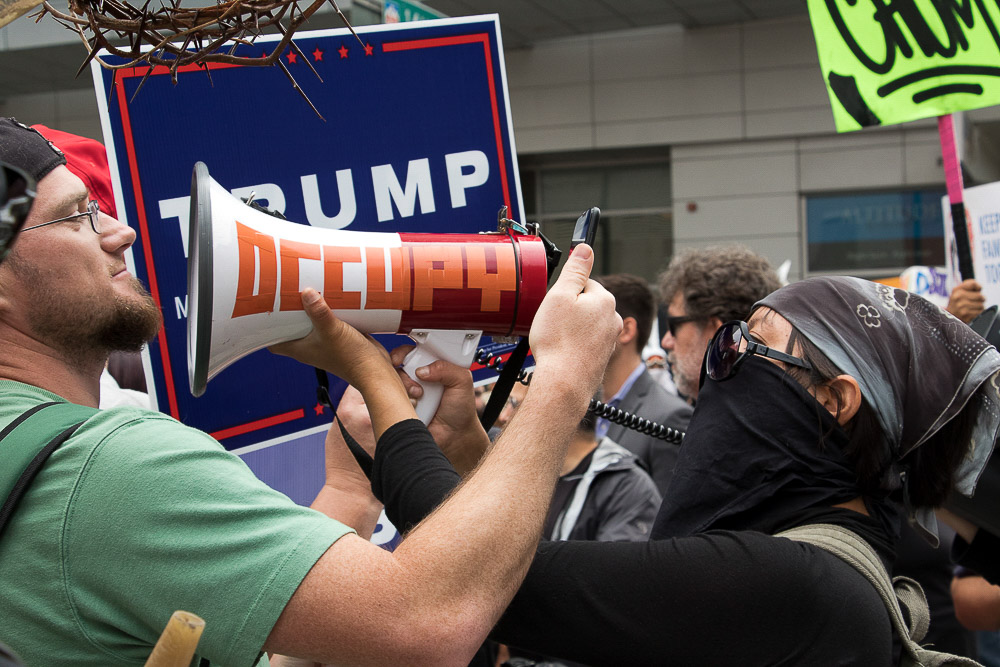 An anti-Trump protester blares music in the face of a Trump supporter. (Chloe Aiello/Denverite)