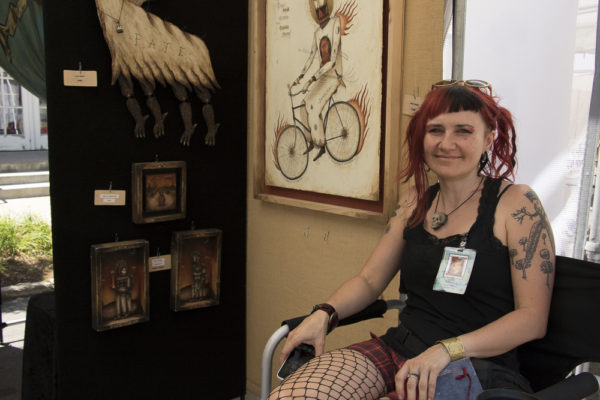 """Ellie Rusinova sits with her """"Dancing Bones"""" exhibit. It is her fifth year at the festival. (Chloe Aiello/Denverite)"""