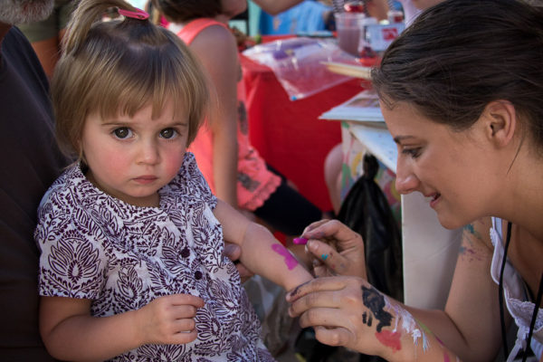 Julia Brown receives butterfly arm paint at the Child Rescue Foundation stand outside of the Cherry Creek Public Library. (Chloe Aiello/Denverite)