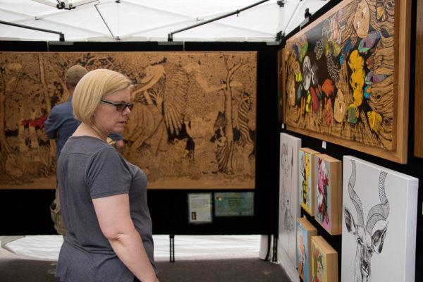 Festival attendees peruse Natacha Monnalisa's art. (Chloe Aiello/Denverite)