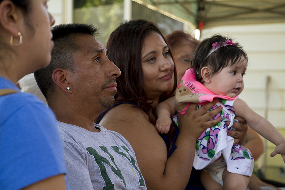 "Liliana Peña holds her daughter during a meeting for Denver Meadows mobile home park residents led by 9 to 5 Colorado organizer Andrea ""Dre"" Chiriboga-Flor. July 6, 2016. (Kevin J. Beaty/Denverite)  denver meadows; affordable housing; trailer park; development; denver; aurora; denverite; kevinjbeaty; colorado;"