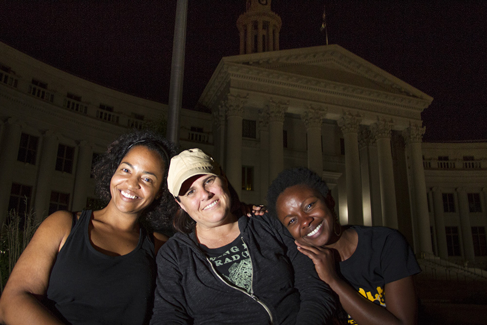 Black Lives Matter Co-Leads Amy E. Emery-Brown and Sasha McGhee (left and right, respectively) and a supported who wished not to be named pose in front of the Denver City and County Building during the first night of a five day occupation at Civic Center Park. July 7, 2016. (Kevin J. Beaty/Denverite)  black lives matter 5280; protest; march; denver; colorado; kevinjbeaty; denverite;