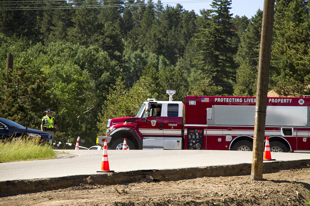 A fire truck drives through a police checkpoint near Nederland's Barker Reservoir while the Cold Springs Fire is being fought nearby. (Kevin J. Beaty/Denverite)  nederland; forest fire; colorado; fire fighting; denverite; kevinjbeaty;
