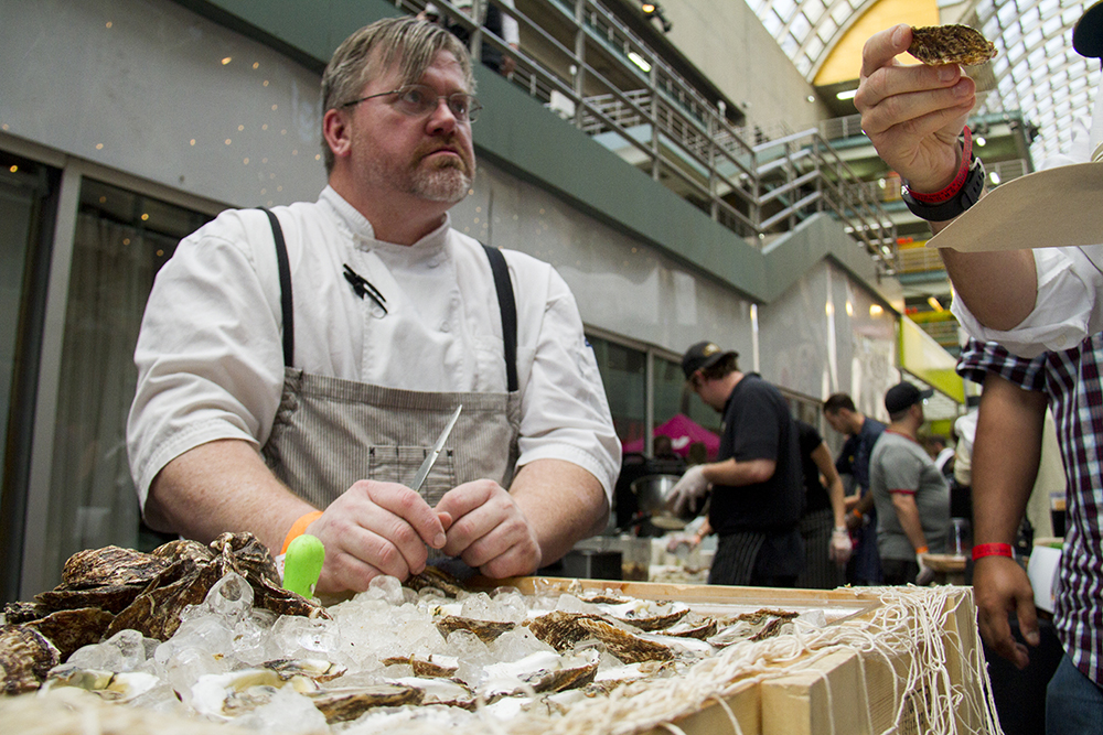 Blue Island Oyster Bar head chef DJ Nagle shucks oysters for patrons during The Big Eat at the Denver Center For The Performing Arts, July 14, 2016. (Kevin J. Beaty/Denverite)  food; big eat; Denver Center For The Performing Arts; denver; kevinjbeaty; colorado; denverite;