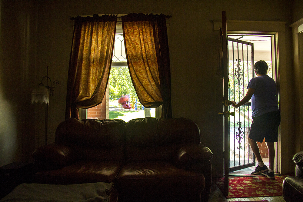 Diane Medina peers through her front door into La Raza Park across the street. (Kevin J. Beaty/Denverite)  la raza park; columbus park; sunnyside; chicano; denver; kevinjbeaty; denverite; colorado;