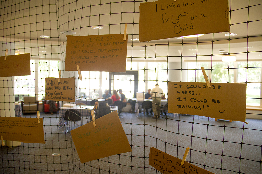 Cardboard signs hang in the Denver Public Library during a day of empathy-fueled events meant to teach people about what it's like to be homeless. (Kevin J. Beaty/Denverite)