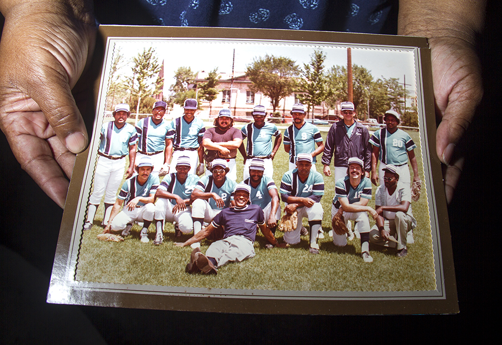 Beverly Buckmon holds up an old photo of the Cloud 7 ballteam. That's Joe Brooks sitting on the ground in the middle. (Kevin J. Beaty/Denverite)  baseball; sports; five points; denver randalls; kevinjbeaty; denver; denverite; kevinjbeaty; colorado;