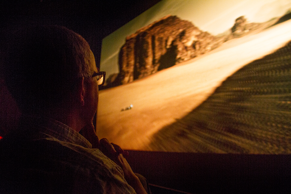 """Dr. Steven Lee watches """"The Martian"""" during a Denver Film Society event at the Denver Museum of Nature and Science. Lee is Department Chair & Curator of Planetary Science at the museum and his work focuses on the interaction of surface and atmosphere on Mars. Needless to say he was the keynote presenter after the film, discussing the planet's weather and geography differ from the on-screen depiction. (Kevin J. Beaty/Denverite)  denver museum of nature and science; dmns; denver film society; dfs; movie; science; mars; denver; kevinjbeaty; colorado; denverite"""