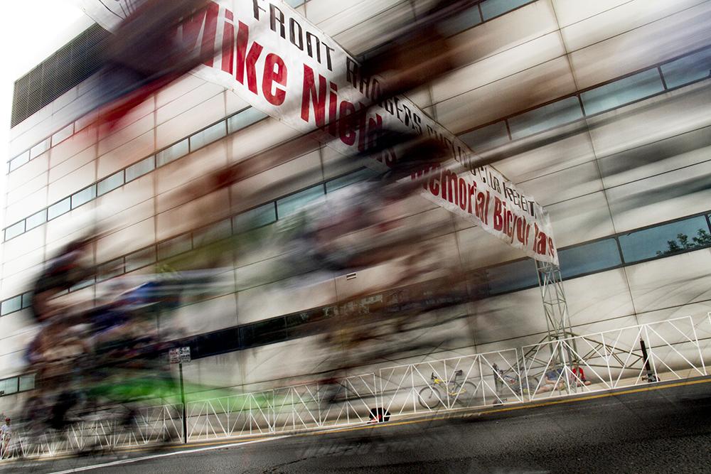 Racers speed past the start/finish line. The Bannock Street Criterium. July 31, 2016. (Kevin J. Beaty)  biking; bike; cycling; golden triangle; bannock street criterium; denver; colorado; sports; kevinjbeaty; denverite;