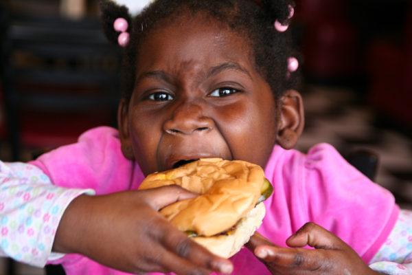 A child gets after a hamburger. (Steven Depolo/Flickr)