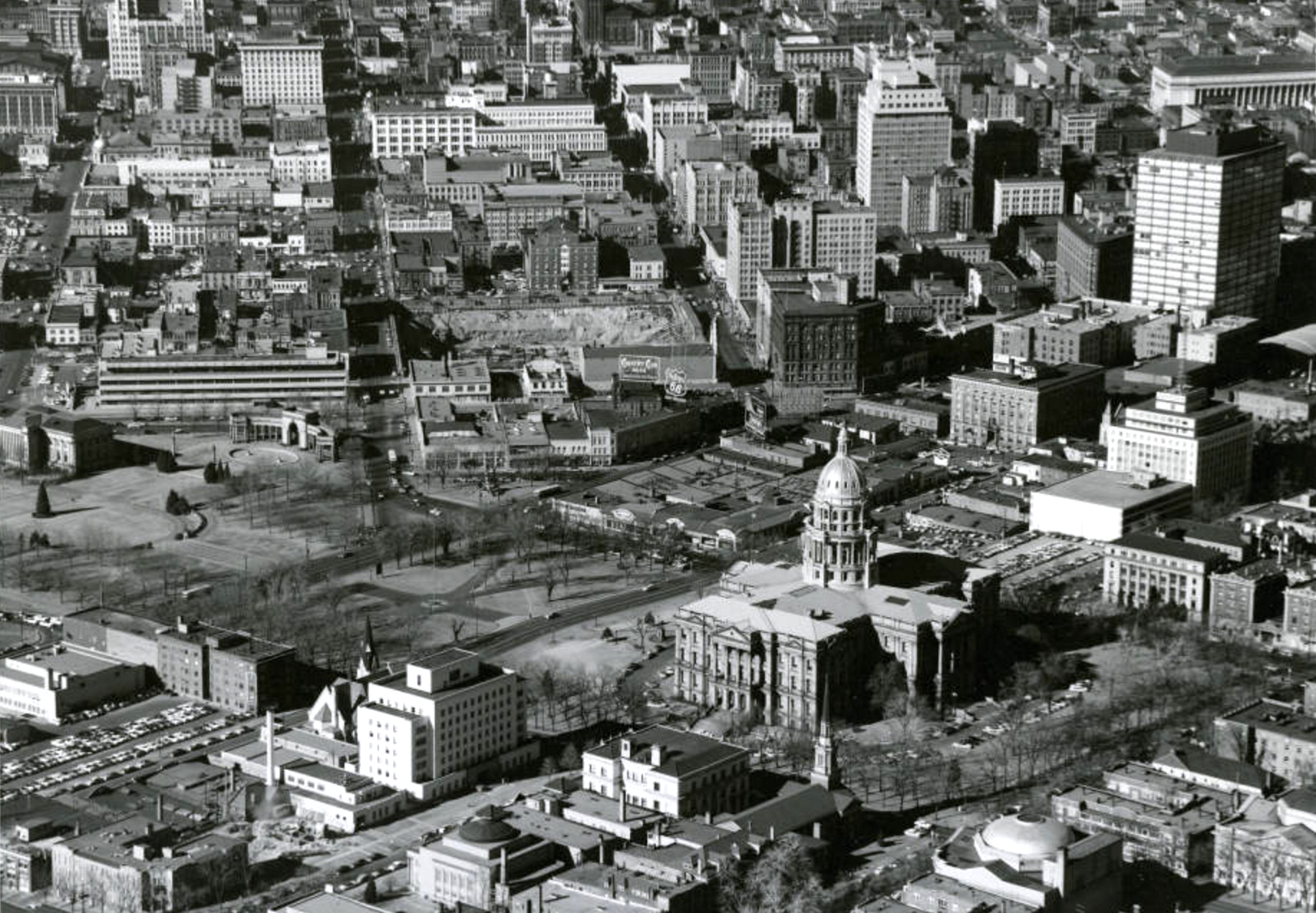 "Aerial view of the Colorado State Capitol building, a park, 15th (Fifteenth) and 16th (Sixteenth) Streets, Broadway and Lincoln Street in the Central Business District of Denver. Colorado. Shows the Denver City and County Building annex, the Carnegie library building, the Voorhies Memorial, reflecting pool and fountains in Civic Center Park, First Presbyterian Church on Broadway, the State Medical Examiners Office, the State Museum, the Colorado State Bank, the Republic Building, the Denver Theater Building, the Conoco building and the Paramount Theater. Businesses line the streets, signs read: ""Gump"" ""Walgreen Drugs"" and ""Used Cars."" Bill boards and standing signs read: ""Country Club Beer, Famous For Its Flavor"" ""Phillips 66 Runs Smoother"" and ""Burlington Route Zephyr."" The excavation site for the Hilton Hotel is on Court Place. (John A. Myers/Denver Public Library/Western History Collection/(Denver Public Library/Western History Collection/Z-11640)  cityscape; capitol hill; civic center; historic; denver public library; dpl; archive; archival; denverite"