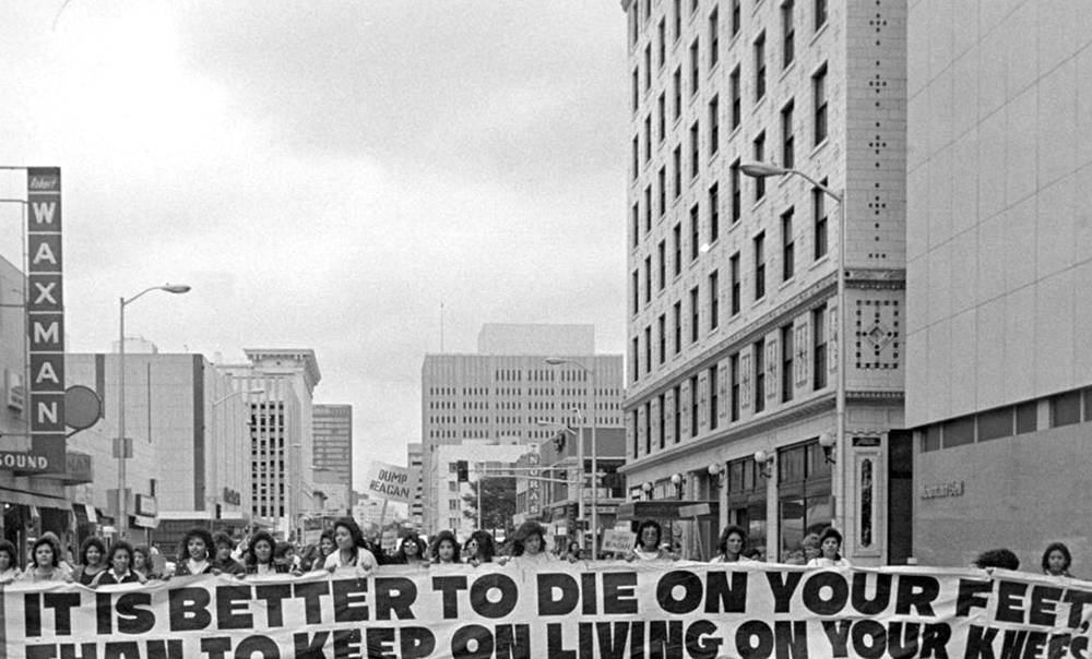 "'Mexican Americans, members of the Crusade for Justice (La Crusada Para Justicia) march in protest down 15th (Fifteenth) street in Denver, Colorado. They carry a large banner written in both English and Spanish, which reads: ""It Is Better to Die On Your Feet Than to Keep On Living On Your Knees"" ""Es Mejor Morir de Pie, Que Seguir Viviendo de Rodillas.""'  Between 1966 and 1970. (Shannon Garcia/Denver Public Library/Western History Collection/AUR-2152)"