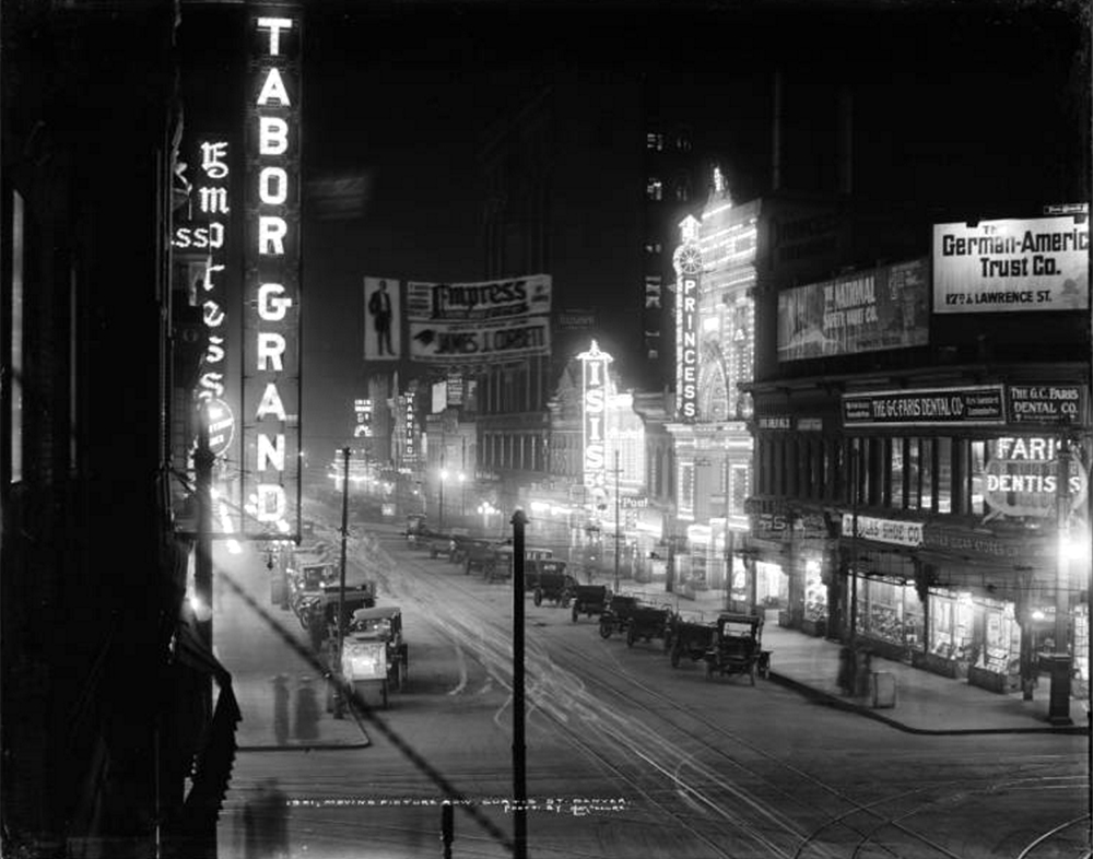 """Night time view of Curtis Street, Denver, Colorado; """"Motion Picture or Theater Row""""; illuminated signs for Tabor Grand (16th & northwest corner of Curtis), Empress (1615-1621 Curtis), Iris Theatre (1746 Curtis), NanKing Chop Suey restuarant (1712 Curtis), Pool Hall, Isis Amusement Company & Theatre (1632 Curtis), Princess Amusement Company & Theater (1620 Curtis), G.C. Faris Dental Company (George C. Faris, 931 16th); non-illuminated billboards, advertisements & signage include Douglas Shoe Company, German American Trust Co., National Safety Vault Company, Royal Bar, Rock Island Lines, """"Learn to dance...six lessons...Caldwell Hall."""" A small outside popcorn or refreshment stand is in foreground left. 1913 (Louis Charles McClure/Denver Public Library/Western History Collection/MCC-1901)  theater row; 16th street; sixteenth street; central business district; historic; archival; archive; denver public library; dpl; denverite"""