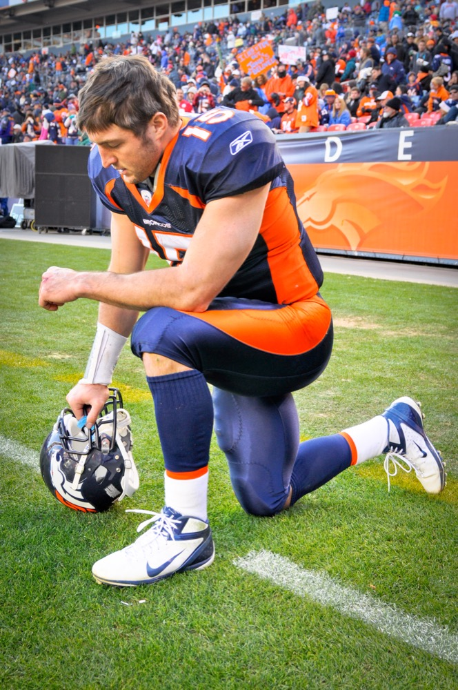"""Tim Tebow """"Tebowing"""" taken on Jan. 1, 2012,  at Sports Authority Field at Mile High.  (Ed Clemente Photography/Wikimedia Commons)"""