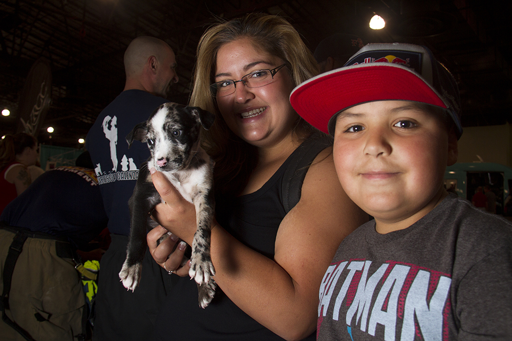 Vanessa and Evan Montoya hold a yet-to-be-named puppy provided by the hunky Fire Rescue Dogs Calendar crew.  Denver Pet Expo. Aug. 21, 2016. (Kevin J. Beaty/Denverite)  denver pet expo; animals; pets; dogs; kevinjbeaty; denver; denverite; colorado;