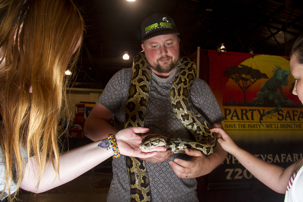 Ryan Starr of Party Safari animal casting services shows Jessica Delaney (left) and Aubrey Martinez Qwerty the Burmese Python at the Denver Pet Expo. Aug. 21, 2016. (Kevin J. Beaty/Denverite)  denver pet expo; animals; pets; dogs; kevinjbeaty; denver; denverite; colorado;