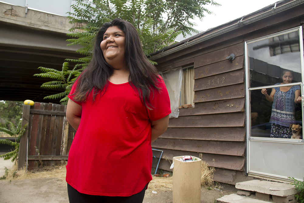 Esmeralda Aguilar outside her home in Elyria Swansea. (Kevin J. Beaty/Denverite)  elyria swansea; i-70; cdot; development; gentrification; denver; denverite; colorado; kevinjbeaty;