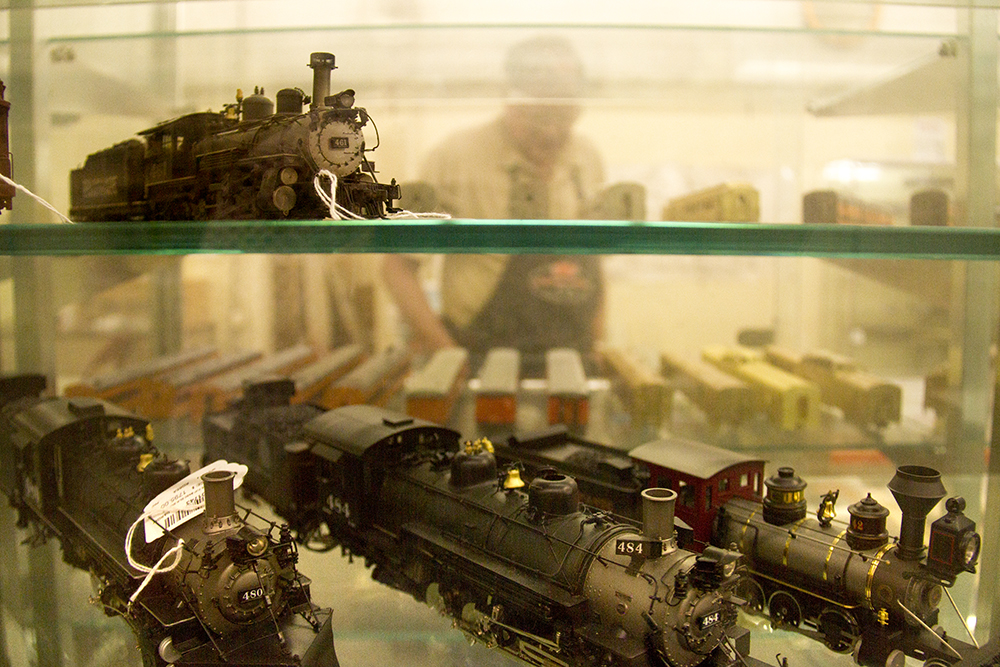Duncan Harvey, who's worked at Caboose Hobby on South Broadway since 1997, can be seen through a display case filled with tiny locomotives. (Kevin J. Beaty/Denverite)  train; caboose hobby; model; denver; south broadway; colorado; kevinjbeaty; denverite;
