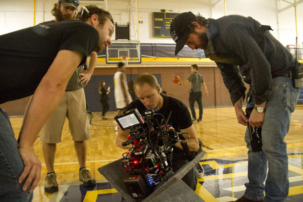 "Colorado-based first assistant camera operator Calvin Sneed (center) adjusts a focus ring between takes during the production of ""Amateur,"" a Netflix feature film being shot at Regis University. (Kevin J. Beaty/Denverite)