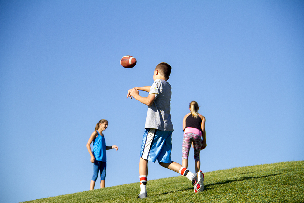 Kids toss footballs during the Denver Broncos Training Camp. (Kevin J. Beaty/Denverite)  broncos; football; training camp; sports; kevinjbeaty; denver; denverite; colorado;